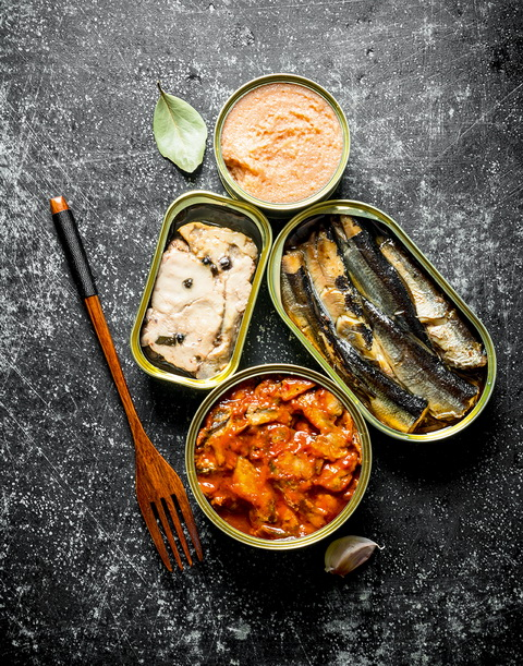 Canned fish in tin cans. On dark rustic background