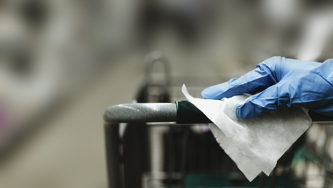Gloved hand with a tissue paper on a shopping cart in a supermarket during the Coronavirus pandemic